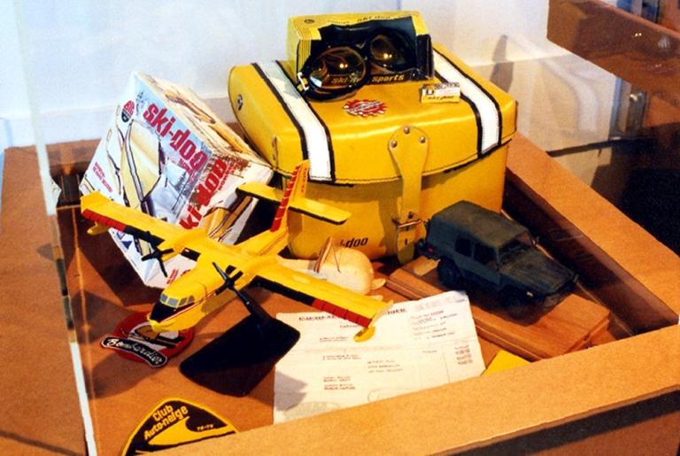 Vitrine présentant une maquette d'un avion amphibie CL-215, une maquette d'un véhicule militaire Iltis, un jouet de motoneige Ski-Doo et des accessoires de motoneige Ski-Doo, exposition temporaire temporaire « Les collections du Musée… Tout un monde à découvrir! », 2000.